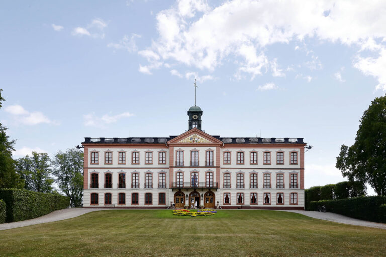 Slott med gräsmatta framför/A castle with a lawn in front of it