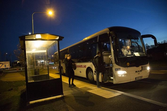 Vit buss vid en busskur på kvällen.