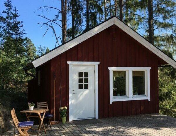 Liten röd stuga med vit dörr och en altan utanför.