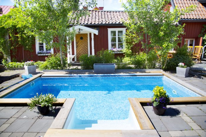 Röd stuga med en pool framför/Red cottage with a pool in front