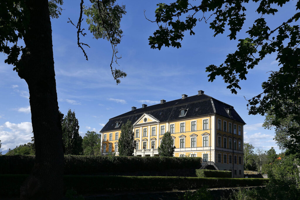 Gult slott med träd i förgrunden/Yellow castle with trees in the foreground