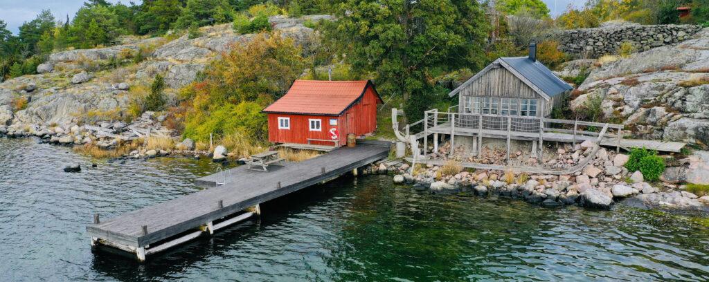 Röd stuga på ö med brygga och vatten framför