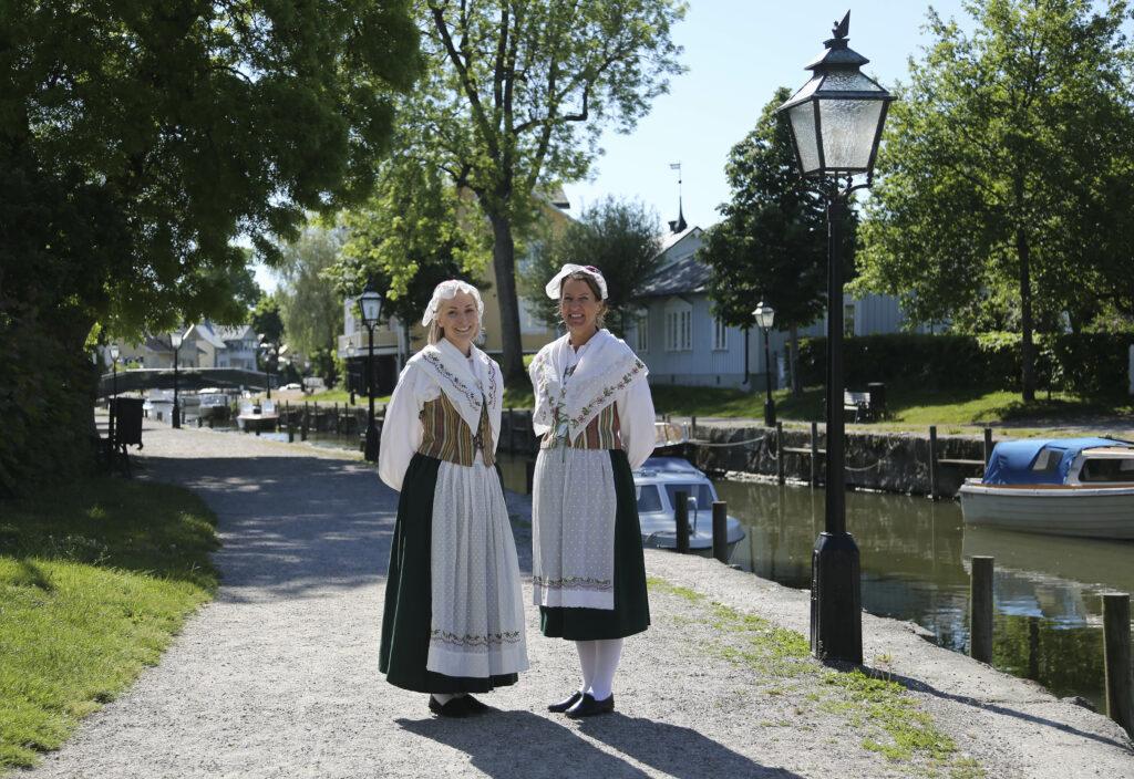 Två kvinnor i Trosa-Vagnhäradsdräkten ståendes vid Trosaån
