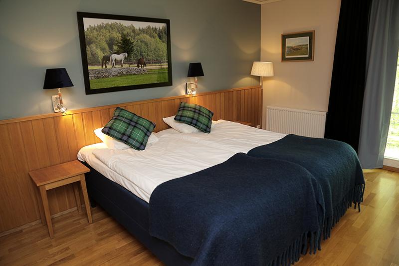 Säng på hotellrum med ett blått överkast/ Bed in hotel room with a blue bedspread