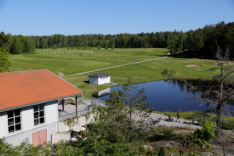 Vy över golfbana med ett hus i vänsterkant och en damm i högerkant/View of golf course with a house on the left edge and a pond on the right edge