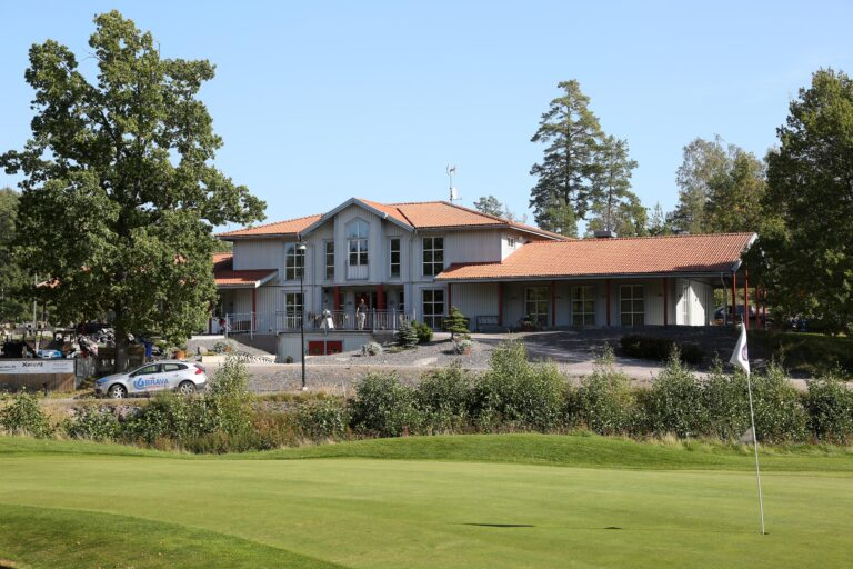 Golfbana med klubbhus i bakgrunden/golf course with clubhouse in the background
