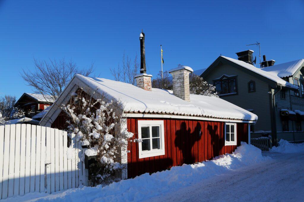 Liten röd stuga på Östra långgatan i vinterskrud