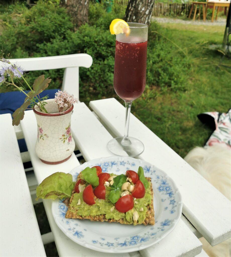 Smörgås och dryck i champagneglas på cafébord/ Sandwich and a drink in a champagne glass on a café table