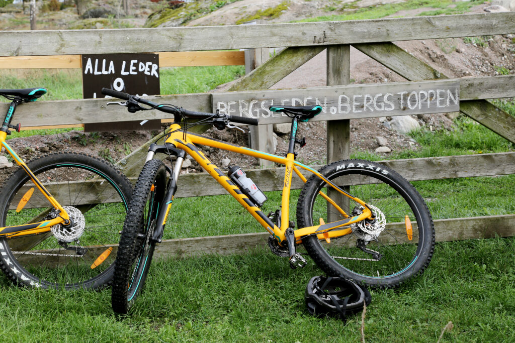 A yellow MTB leaning to a fence