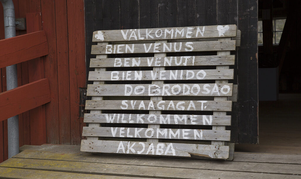 A sign that says welcome in various languages