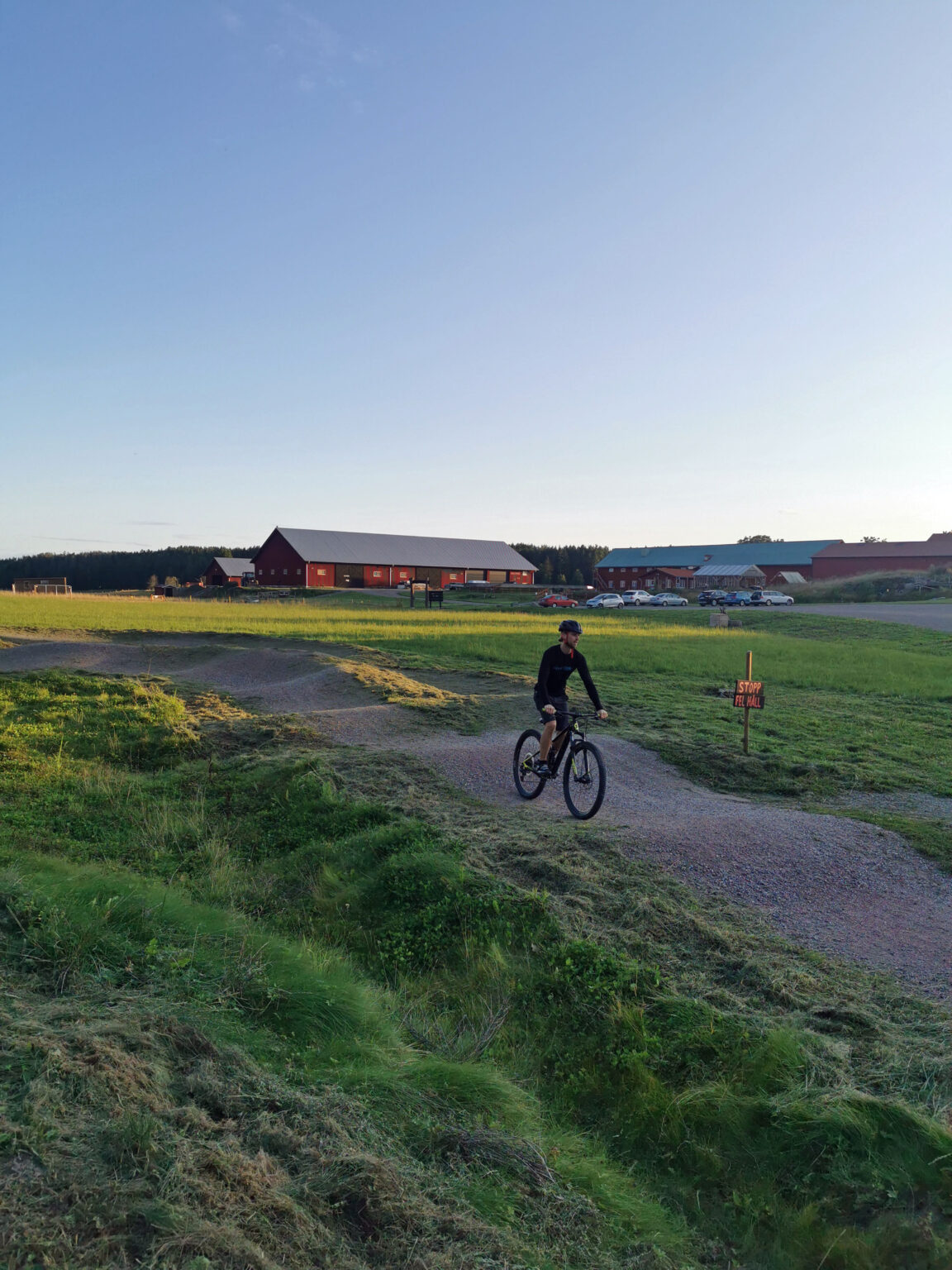 Man biking at a pumptrack with green fields and red barns in the background.